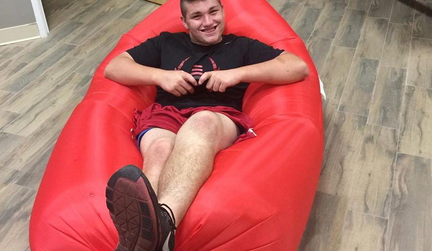 """In this photo provided by NOVA Home Loans Arizona Bowl, a worker from the Arizona Bowl shows off one of the inflatable """"Big Lazy"""" couches that is part of bowl gifts being given to players for the Dec. 29 game. The couch is one of the unique items as the 41 bowl games try to provide something different.  (NOVA Home Loans Arizona Bowl via AP)"""