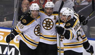 Boston Bruins center Patrice Bergeron (37) celebrates his second period goal with teammates David Pastrnak (88), Brad Marchand (63), obscured, and Torey Krug (47) during play against the Florida Panthers in an NHL hockey game, Thursday, Dec. 22, 2016, in Sunrise, Fla. (AP Photo/Joe Skipper)