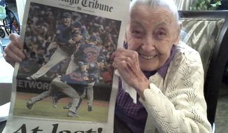 """In this Nov. 4, 2016 photo provided by the Strobel Family, Cubs fan Helen Weithman, celebrates the Chicago Cubs World Series victory at her home in Glen Ellyn, Ill. A lifelong Cubs fan Weithman, 98, who according to family was slipping away until the Cubs made it to The World Series, """"She really came alive when it started and they had the Cubs games on,"""" said the daughter, Kathleen Strobel. Weithman died on Nov. 29, 2016 after finally seeing the Cubs win the series for first time in her lifetime. (Photo Courtesy of the Strobel Family via AP)"""
