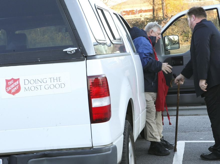 ADVANCE FOR USE SATURDAY, DEC. 24 - In this Dec. 9, 2016 photo, Lt. Robert Dolby, right, of the Salvation Army helps James White  to his position of ringing a bell outside of Quality Foods in Anderson, S.C. He's been out in the community to welcome Christmas shoppers every year since 1995, typically ringing the bell for 40 hours a week or more, (Ken Ruinard/The Independent-Mail via AP)