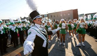 ADVANCE FOR WEEKEND EDITIONS - In this Saturday, Oct. 22, 2016, photo, Marshall University Marching Thunder Drum Major Mary Bunten leads the band in a performance as Marshall fans tailgate prior to the start of the Thundering Herd's football game against Louisville at Joan C. Edwards Stadium in Huntington, W.Va. The Marching Thunder will perform in the Rome New Year's Day Parade in Rome, Italy, on Jan. 1, 2017. (Sholten Singer/The Register-Herald via AP)