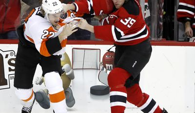 Philadelphia Flyers right wing Dale Weise, left, and New Jersey Devils defenseman Seth Helgeson fight during the first period of an NHL hockey game, Thursday, Dec. 22, 2016, in Newark, N.J. (AP Photo/Julio Cortez)