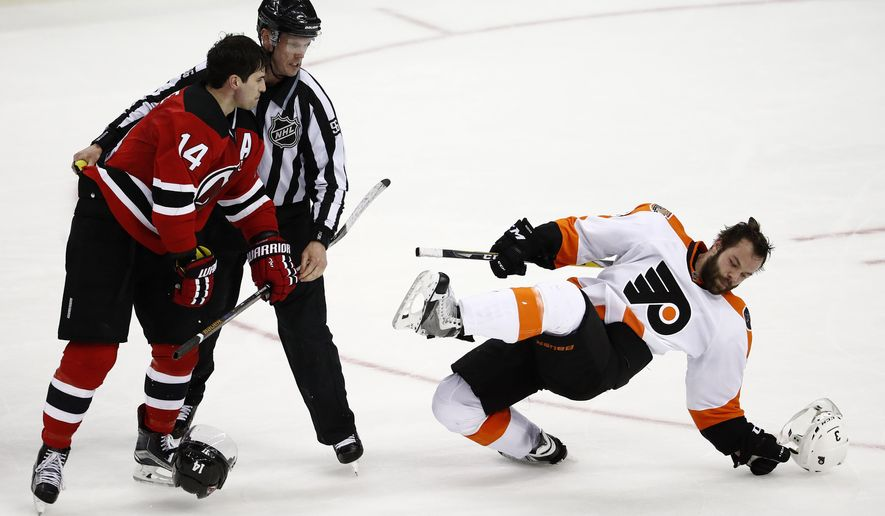 Philadelphia Flyers defenseman Radko Gudas, right, of the Czech Republic, falls down after being pushed by New Jersey Devils center Adam Henrique, left, as linesman David Brisebois (96) intervenes during the third period of an NHL hockey game, Thursday, Dec. 22, 2016, in Newark, N.J. The Devils won 4-0. (AP Photo/Julio Cortez)