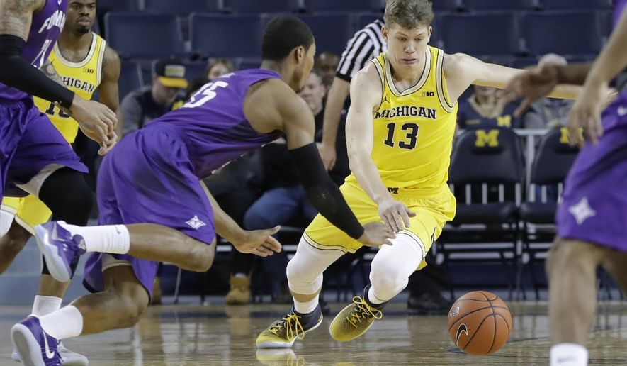 Furman guard Daniel Fowler (35) and Michigan forward Moritz Wagner (13) chase the ball during the first half of an NCAA college basketball game, Thursday, Dec. 22, 2016, in Ann Arbor, Mich. (AP Photo/Carlos Osorio)