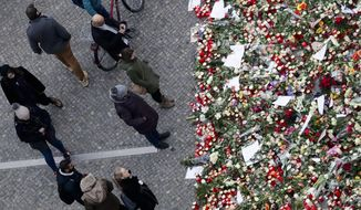 People stand near candles at the Christmas market, three days after a truck ran into the crowd and killed several people, near the Kaiser Wilhelm Memorial Church in Berlin, Thursday, Dec. 22, 2016. (AP Photo/Markus Schreiber)