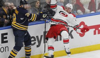 Buffalo Sabres forward Zemgus Girgensons (28) and Carolina Hurricanes defenseman Matt Tennyson (26) collide during the second period of an NHL hockey game, Thursday, Dec. 22, 2016, in Buffalo, N.Y. (AP Photo/Jeffrey T. Barnes)