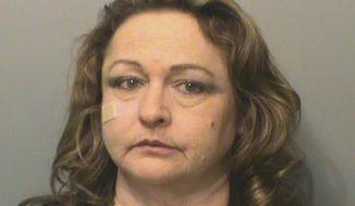 "This Wednesday, Dec. 21, 2016 booking photo released by Polk County Sheriff's office, Susan Ackerman at the Polk County Jail in Des Moines, Iowa. The former administrative law judge for Iowa Workforce Development has been charged with fraud for allegedly adding her ineligible daughter to her state insurance plan, in a case that her supporters are calling politically motivated. In 2014, Ackerman helped expose ""perceived pressure"" on judges to favor employers over jobless workers in disputes over unemployment benefits. (Polk County Sheriff's Office via AP)"