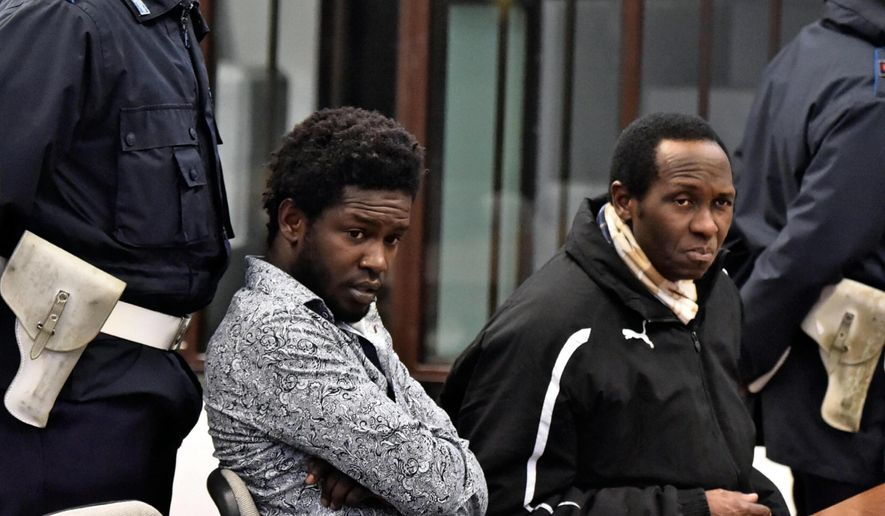 Cheik Tidiane Diaw, from Senegal, left, sits next to an unidentified interpreter in a courtroom in Florence, Italy, Thursday, Dec. 22, 2016. A Florence court is debating the fate of Diaw, who is accused of murdering an American woman, Ashley Olsen, in her flat after they met at a nightclub in January 2016.  (Maurizio degl'Innocenti/ANSA via AP)