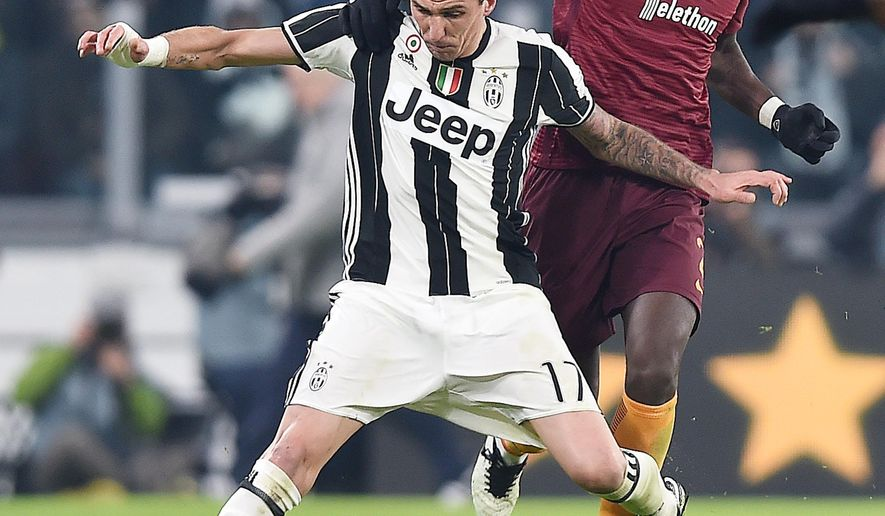 Juventus' Mario Mandzukic, left, is challenged by Roma's Antonio Rudiger during a Serie A soccer match, at the Juventus Stadium in Turin, Italy, Saturday, Dec. 17, 2016. (Andrea Di Marco/ANSA via AP)