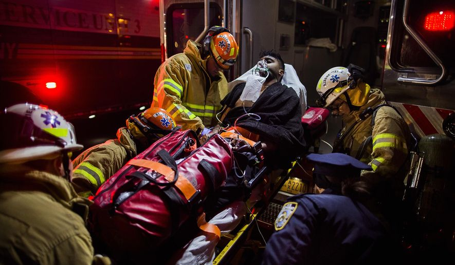 Firefighters load an injured person into an ambulance during a fire on the west side of Manhattan in New York, Thursday, Dec. 22, 2016. About a dozen people, including a few firefighters, have been injured in the fire at a high-rise building on Manhattan's Upper West Side. (AP Photo/Andres Kudacki)