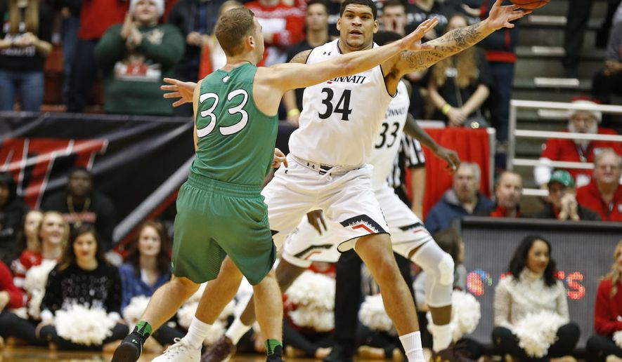 Cincinnati guard Jarron Cumberland (34) tips a pass off the hand of Marshall guard Jon Elmore (33) during the first half of an NCAA college basketball game, Thursday, Dec. 22, 2016, in Cincinnati. (AP Photo/Gary Landers)