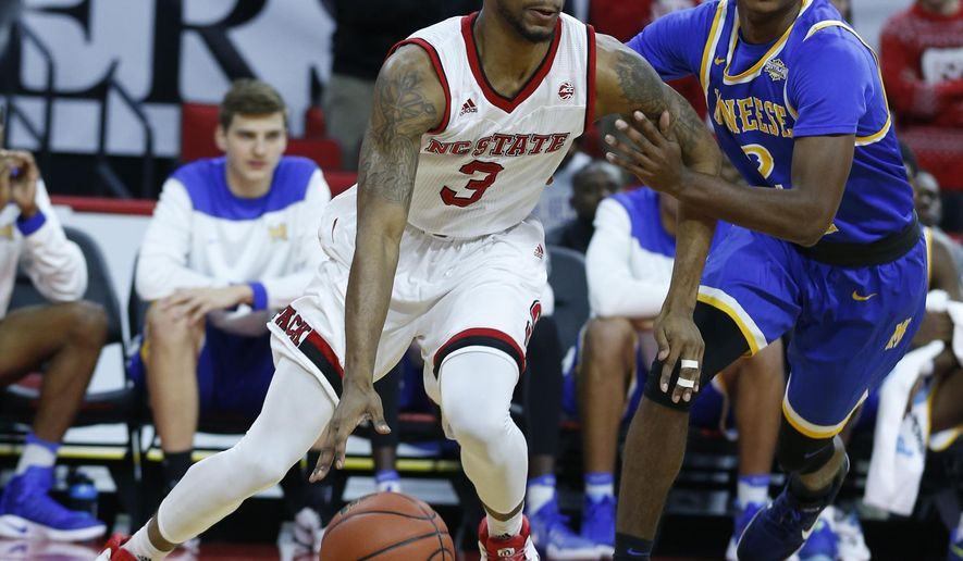 North Carolina State's Terry Henderson (3) drives around McNeese's James Harvey (2) during the first half of an NCAA college basketball game, Thursday, Dec. 22, 2016 in Raleigh, N.C. (Ethan Hyman/The News & Observer via AP)