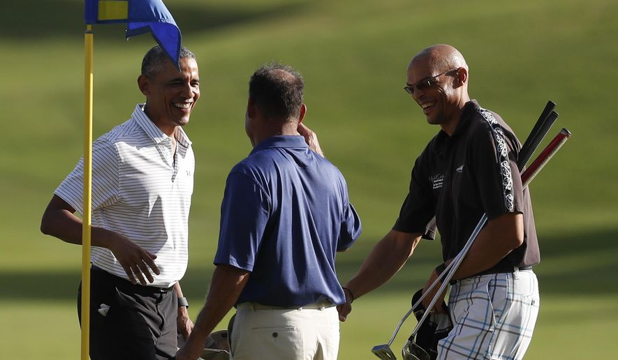 President Barack Obama, left, smiles after putting on the 18th green at Kapolei Golf Club, in Kapolei, Hawaii, Wednesday, Dec. 21, 2016. Golfing with the president from left are Bobby Titcomb, and Darrell Harrington. (AP Photo/Carolyn Kaster)