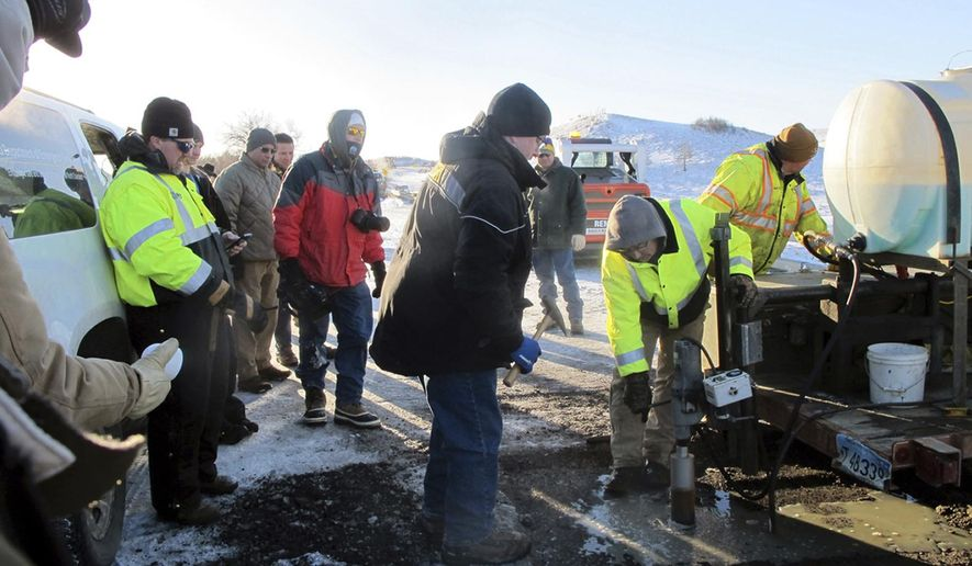 North Dakota Department of Transportation bridge engineer John Ketterling, center, watches while a work crew pulls a concrete core sample from the Backwater Bridge over Cantapeta Creek Thursday, Dec. 22, 2016, near Cannon Ball, N.D, to determine if repairs are needed after a vehicle was burned on the bridge during Dakota Access Pipeline protest activities. (Lauren Donovan/The Bismarck Tribune via AP)