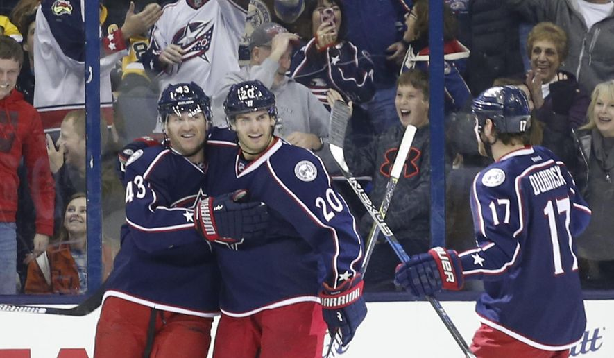 Columbus Blue Jackets' Scott Hartnell, left, celebrates his hat trick against the Pittsburgh Penguins with teammates Brandon Saad, center, and Brandon Dubinsky during the third period of an NHL hockey game Thursday, Dec. 22, 2016, in Columbus, Ohio. (AP Photo/Jay LaPrete)