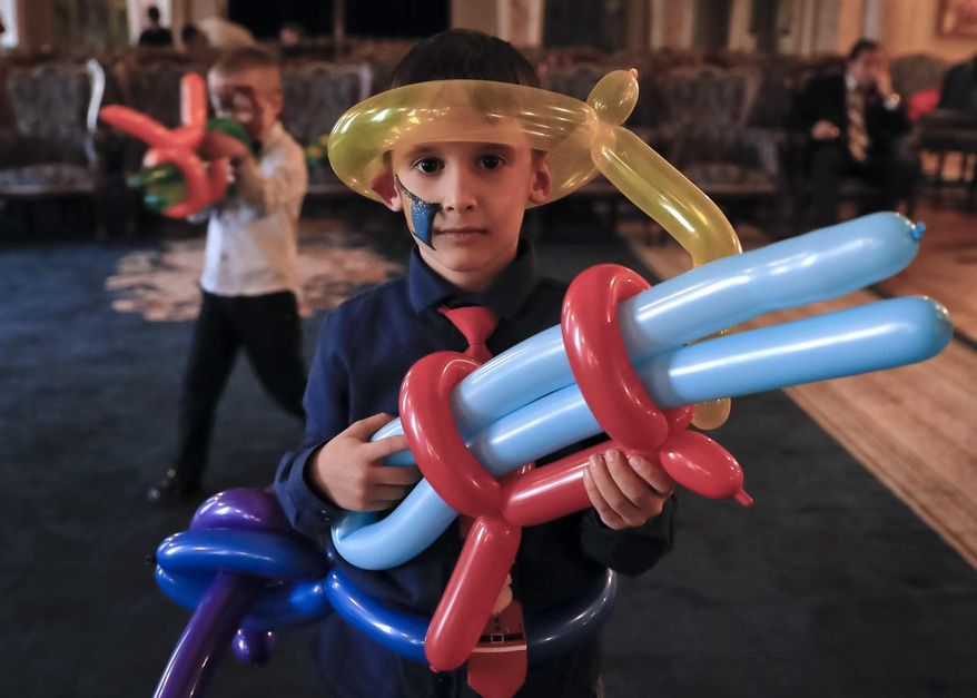 In this Tuesday, Dec. 13, 2016 photo, 6 year old Robert poses with balloons shaped to resemble a weapon during a Christmas show for children of Romanian military families, in Bucharest, Romania. Romania's defense ministry has laid on a Christmas party at the grand Palace of the National Military Circle in Bucharest bringing together the sons and daughters of Romanian soldiers who were slain or wounded while on peacekeeping missions overseas. (AP Photo/Vadim Ghirda)