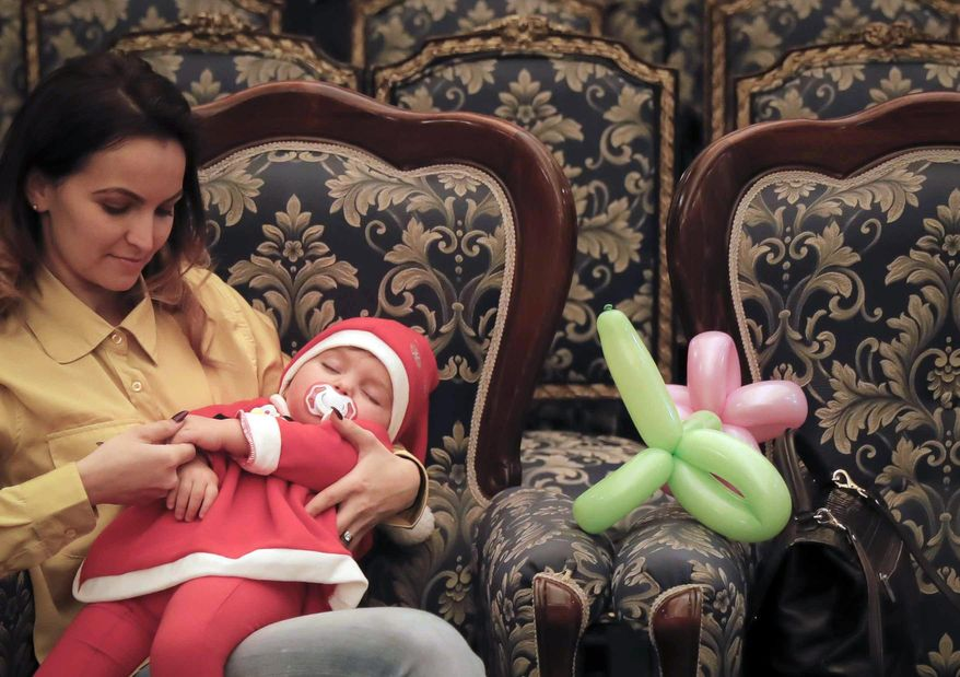 In this Tuesday, Dec. 13, 2016 photo, 19 month old Maya sleeps in her mother's arms after a Christmas show for children of Romanian military families, in Bucharest, Romania. Romania's defense ministry has laid on a Christmas show for dozens of Romanian children whose fathers were killed or injured serving in international peacekeeping missions at the National Military Circle, a grand 19th-century building in downtown Bucharest. (AP Photo/Vadim Ghirda)