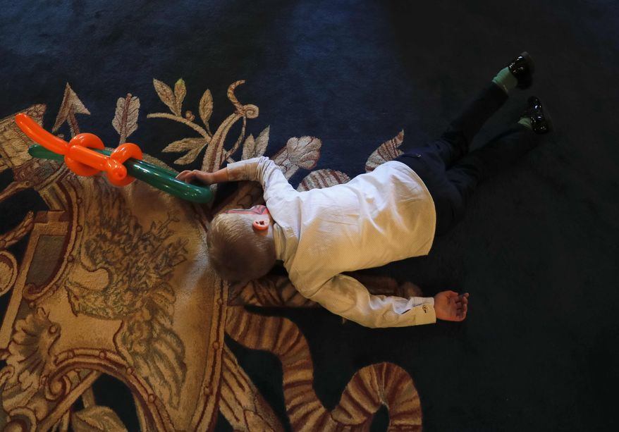 In this Tuesday, Dec. 13, 2016 photo, a boy lays on the floor and holds balloons shaped to resemble a weapon while playing with other children during a Christmas show for children of Romanian military families, in Bucharest, Romania. Romania's defense ministry has laid on a Christmas show for dozens of Romanian children whose fathers were killed or injured serving in international peacekeeping missions at the National Military Circle, a grand 19th-century building in downtown Bucharest. (AP Photo/Vadim Ghirda)