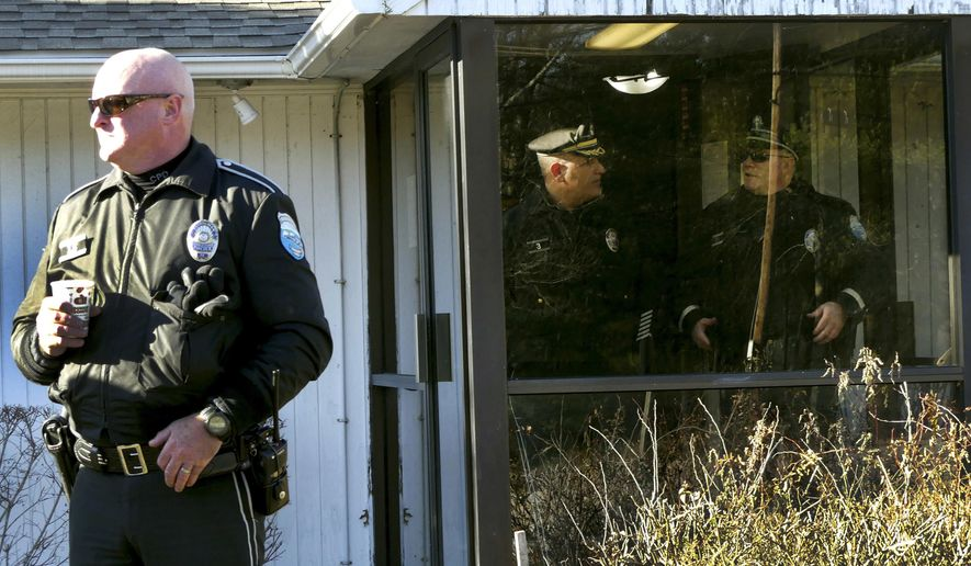 In this Tuesday, Dec. 20, 2016 photo Charlestown, R.I. patrol officer Kevin Ryan, left, stands outside an entrance to the Narragansett tribe's administration building in Charlestown after a faction of the tribe took over the building. Members of a recently elected Narragansett Tribal Council said they took over the administration building Tuesday, Dec. 20 because Chief Sachem Matthew Thomas has refused to relinquish power after they impeached him in October. (Harold Hanka/The Sun via AP)
