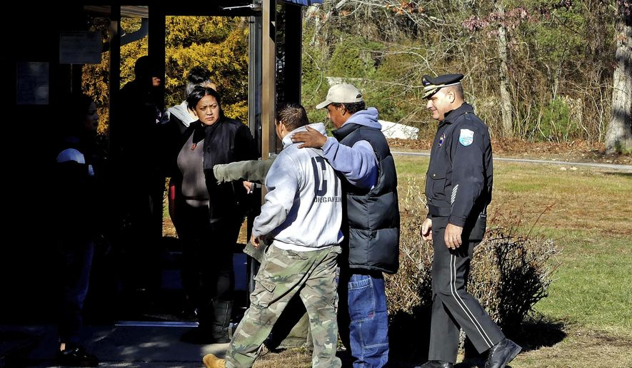 In this Tuesday, Dec. 20, 2016 photo a man is led into the Narragansett tribe's administration building following a minor scuffle near the entrance to the building, in Charlestown, R.I. Members of a recently elected Narragansett Tribal Council said they took over the administration building Tuesday, Dec. 20 because Chief Sachem Matthew Thomas has refused to relinquish power after they impeached him in October. (Harold Hanka/The Sun via AP)