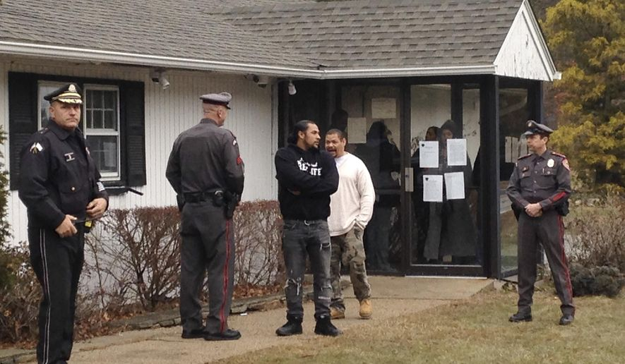 Law enforcement officials, left, and right, stand near opponents of Narragansett Chief Sachem Matthew Thomas outside an entrance to the tribe's administration building, Thursday, Dec. 22, 2016, in Charlestown, R.I. A faction of the tribe opposed to Thomas has been occupying the administration building since Tuesday. Two competing factions, each calling themselves the Narragansett Tribal Council, claim to be the leaders of Rhode Island's only federally recognized tribe. (AP Photo/Jennifer McDermott)