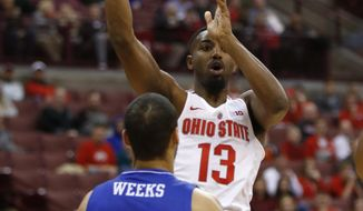 Ohio State guard JaQuan Lyle, right, passes against UNC-Asheville forward Will Weeks during the first half of an NCAA college basketball game in Columbus, Ohio, Thursday, Dec. 22, 2016. (AP Photo/Paul Vernon)
