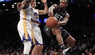 Brooklyn Nets guard Sean Kilpatrick passes the ball around Golden State Warriors forward Kevin Durant during the first half of an NBA basketball game Thursday, Dec. 22, 2016, in New York. (AP Photo/Adam Hunger)