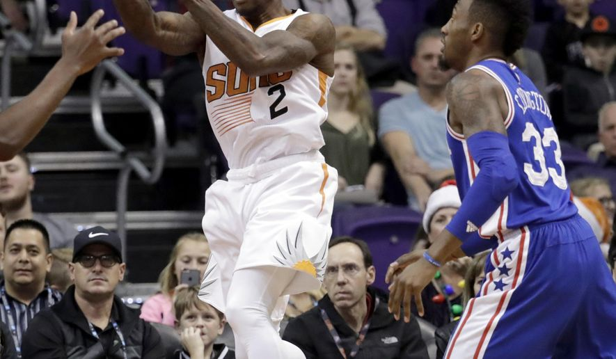 Phoenix Suns guard Eric Bledsoe (2) passes over Philadelphia 76ers forward Robert Covington (33) during the first half of an NBA basketball game, Friday, Dec. 23, 2016, in Phoenix. (AP Photo/Matt York)