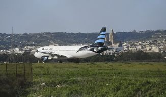 An Afriqiyah Airways plane from Libya stands on the tarmac at Malta's Luqa International airport, Friday, Dec. 23, 2016. Malta's state television says two hijackers who diverted a Libyan commercial plane to the Mediterranean island nation have threatened to blow it up. (AP Photo/Jonathan Borg)