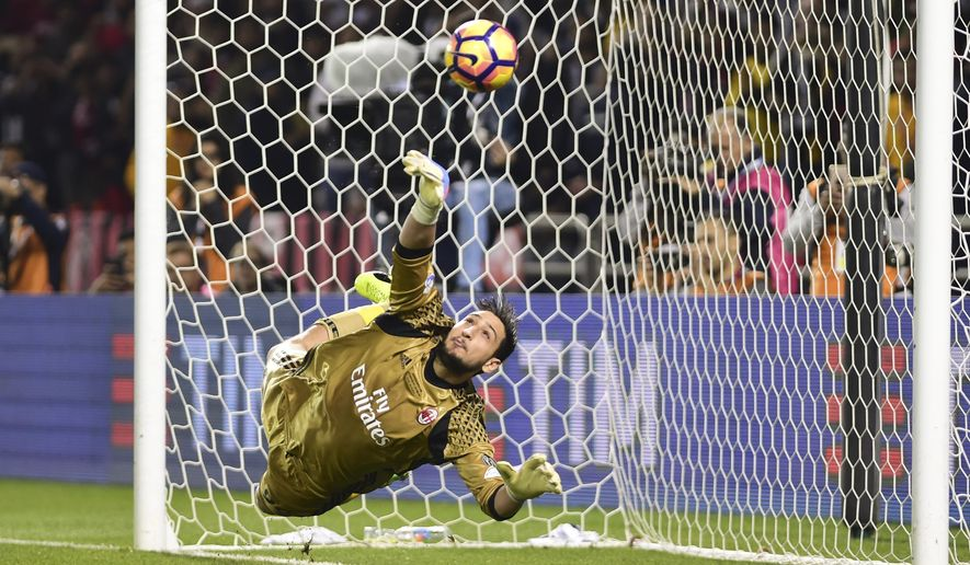 AC Milan goalkeeper Gianluigi Donnarumma saves a penalty during the Italian Super Cup soccer match between Juventus and AC Milan, at the Al Sadd Sports Club in Doha, Qatar, Friday, Dec. 23, 2016. AC Milan won 5-4 following a penalty shootout. (AP Photo/Alexandra Panagiotidou)