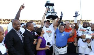 In this image provided by Old Dominion University,  ODU coach Bobby Wilder, center, and his team celebrate after their24-20 win over Eastern Michigan in the Bahamas Bowl NCAA college football game, Friday, Dec. 23,2016, in Nassau, Bahamas. (Jason Coper/Old Dominion University via AP)
