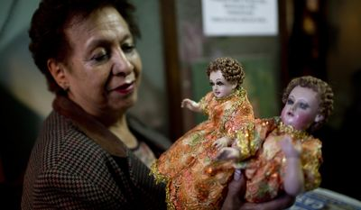 """In this Dec. 16, 2016 photo, Leyla Fuentes holds dolls of infant Jesus after they were restored at Roberto Ramos' workshop in La Paz, Bolivia. Fuentes, a client who inherited the Jesus figures from her grandparents, said she was happy with how hers came out. """"Without baby Jesus there is no Christmas,"""" she said. (AP Photo/Juan Karita)"""