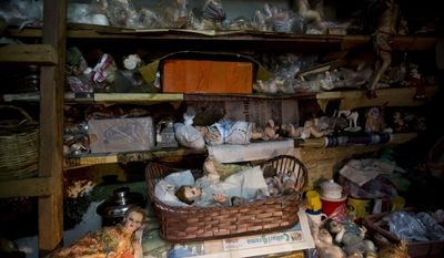 In this Dec. 14, 2016 photo, dolls of infant Jesus fill the shelves of Roberto Ramos' workshop where he restores religious statues in La Paz, Bolivia. At Ramos' tiny workshop, inside an old house in the center of La Paz, dozens of figurines with mangled fingers, dead eyes, haggard faces and dusty hair arrive for him to revive. (AP Photo/Juan Karita)