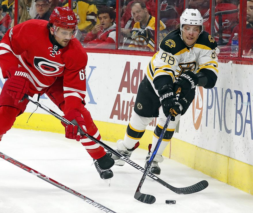 Carolina Hurricanes' Ron Hainsey (65) battles Boston Bruins' David Pastrnak (88) for the puck during the first period of an NHL hockey game, Friday, Dec. 23, 2016, in Raleigh, N.C. (AP Photo/Karl B DeBlaker)