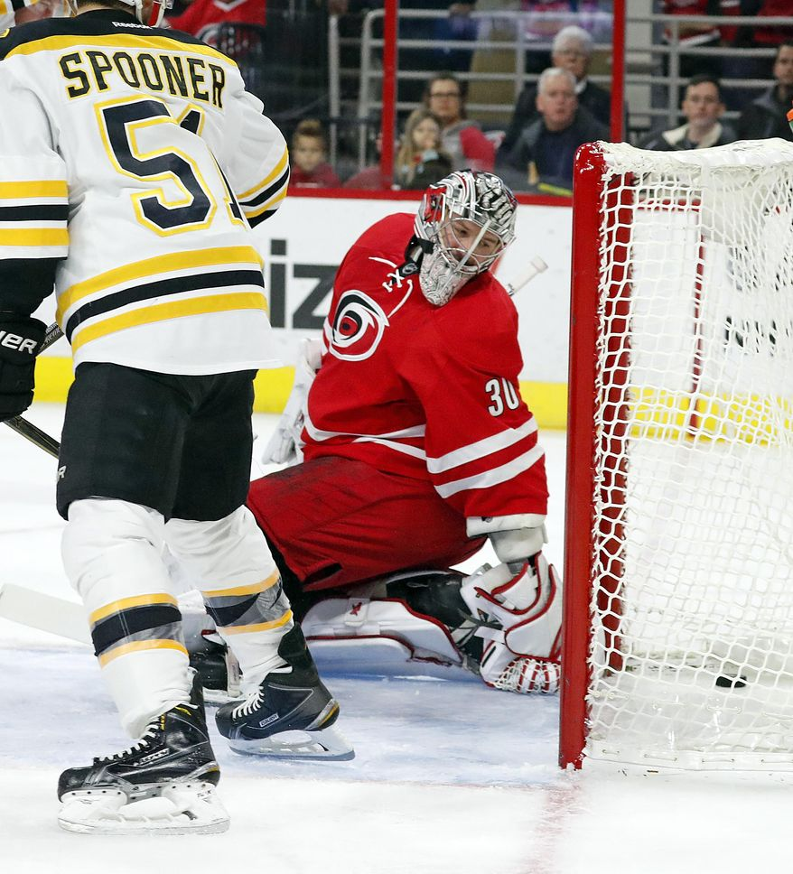 Carolina Hurricanes goalie Cam Ward (30) eyes the puck in the back of the net after it redirected off Boston Bruins' Ryan Spooner (51) skate for a goal during the first period of an NHL hockey game, Friday, Dec. 23, 2016, in Raleigh, N.C. (AP Photo/Karl B DeBlaker)