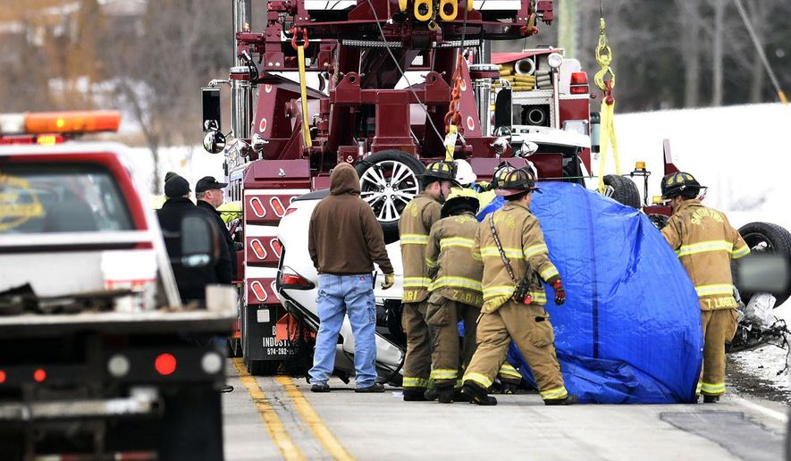 Members of the Smith Township Fire Department work to extricate the body of a man from a vehicle on Thursday, Dec. 22, 2016, north of Churubusco, Ind. Police said the head-on collision between the motor coach and an SUV in the northeastern part of the state was fatal. The bus, owned by Barons Bus, was traveling from Chicago to Columbus, Ohio. (Chad Ryan/The Journal-Gazette via AP)
