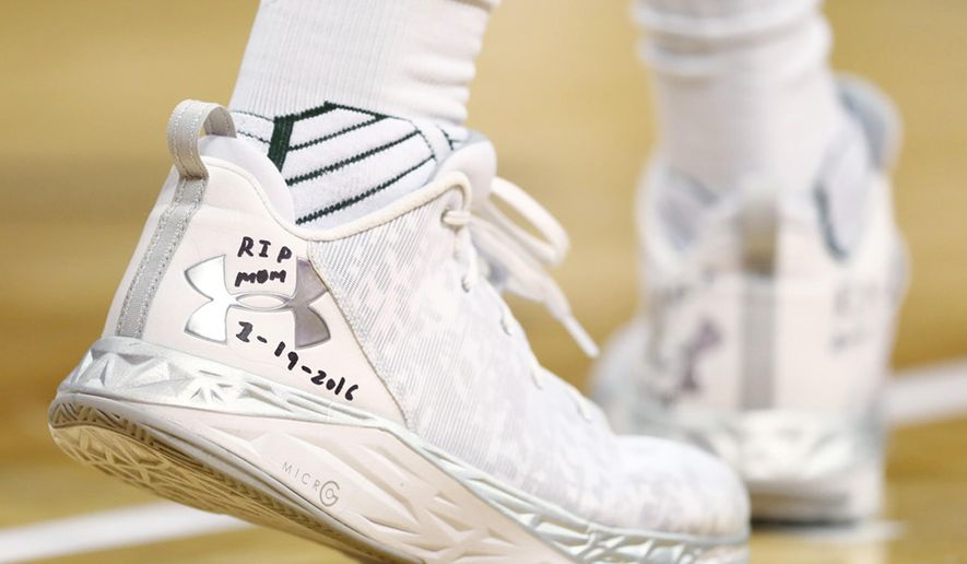 In this Saturday, Dec. 17, 2016, photo, a tribute written in marker is shown on the heel cap of the right shoe worn by Colorado State forward Emmanuel Omogbo during the team's NCAA college basketball game against Kansas State in Denver. Omogbo has dedicated the heel cap on his right shoe to his parents' names, Samson and Caroline, and the heel cap of his left shoe to his sister's twins' names, Israel and Anna. The four died in a house fire in Maryland on Jan. 19, 2016. (AP Photo/David Zalubowski)