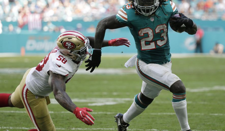FILE - In this Nov. 27, 2016, file photo, Miami Dolphins running back Jay Ajayi (23) runs for a touchdown ahead of San Francisco 49ers outside linebacker Eli Harold (58), during the first half of an NFL football game, in Miami Gardens, Fla. The Dolphins will play the Buffalo Bills on Saturday, Dec. 24. (AP Photo/Wilfredo Lee, File)