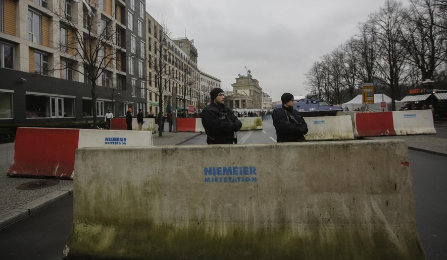Armed police officers stand behind concrete blocks for protection near the Brandenburg Gate in Berlin, Friday, Dec. 23, 2016, after Anis Amri, the suspect of the terrorist attack on a Christmas market in Berlin was shot in Milan, Italy. (AP Photo/Markus Schreiber)