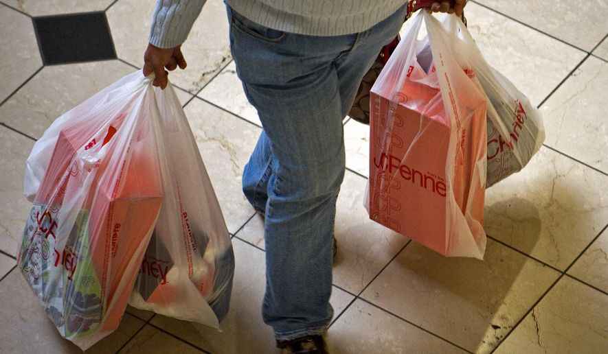 FILE - In this Sunday, Dec. 26, 2010, file photo, a shopper at the Brea Mall in Brea, Calif., carries bags full of packages. Amid the holiday decorations and cheerful ads, splurging is not an option for many Americans struggling to get by. (Michael Goulding/The Orange County Register via AP, File)