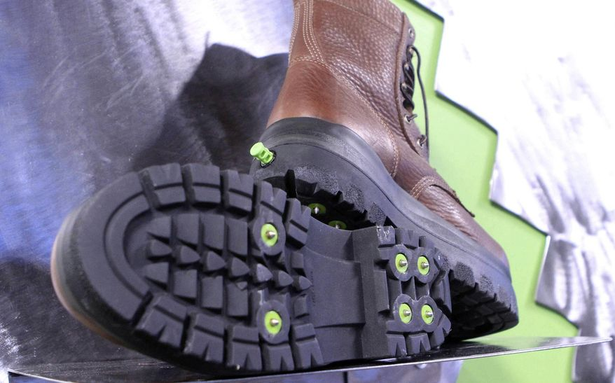 In this Thursday, Nov. 10, 2016 photo, a display shows the bottom and back of boots at the KickSpike store in Anchorage, Alaska. Activate the green button on the back of the boot heel and 7mm steel cleats pop out. Kick the button again and the cleats retract, allowing the wearer to walk inside without tearing up floors. The boots are a new option for walking safely in Anchorage, where ice can be found on streets up to seven months per year. (AP Photo/Dan Joling)