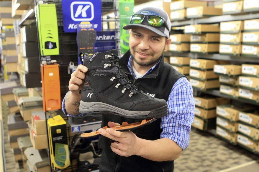 In this Tuesday, Nov. 11, 2016, photo, Stewart Valladolid, boot buyer at B&J Sporting Goods, demonstrates a boot by Korkers featuring interchangeable outer soles with and without studs in Anchorage, Alaska. The boots are one of many safe walking options for Anchorage residents who see ice on streets up to seven months per year. (AP Photo/Dan Joling)