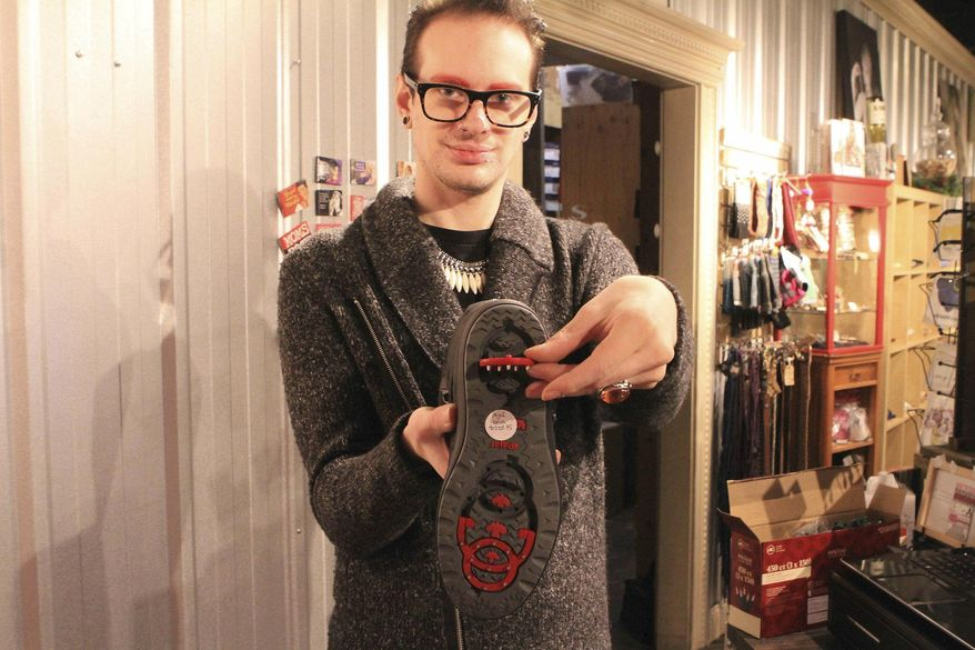 In this Tuesday, Nov. 29, 2016 photo, Tyler Johnson, a sales associate at ShuzyQ boutique, demonstrates a boot by Pajar with hinged inserts on the bottom containing studs that can be flipped out to walk on ice in Anchorage, Alaska. The boots are one of many options available to Anchorage residents for walking on streets with ice up to seven months per year. (AP Photo/Dan Joling)