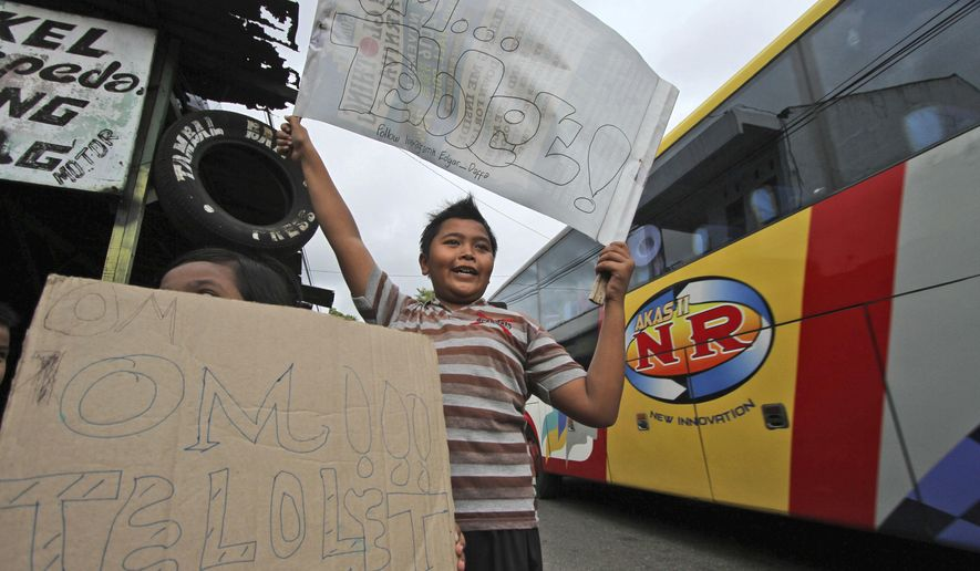 "Indonesian youths display ""om telolet om"" posters asking for passing bus drivers to toot their horns on the side of a road in Solo, Central Java, Friday, Dec. 23, 2016. The phrase got picked up online. International DJs have released mixes with om telolet om honks and social media feeds have been spammed with om telolet om messages followed by bus icons. (AP Photo)"