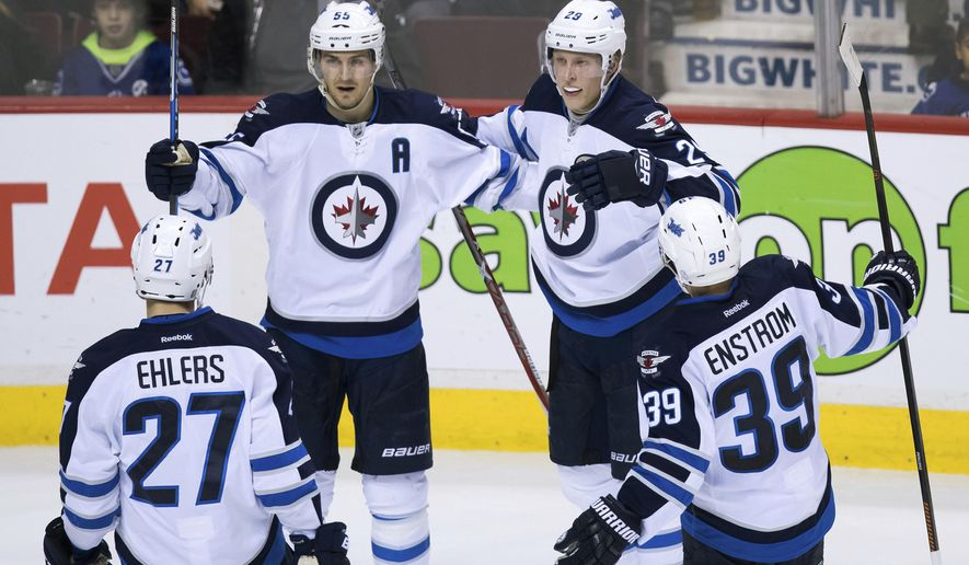 Winnipeg Jets' Nikolaj Ehlers, of Denmark; Mark Scheifele; Patrik Laine, of Finland; and Toby Enstrom, of Sweden, from left, celebrate Laine's goal against the Vancouver Canucks during the second period of an NHL hockey game Thursday, Dec. 22, 2016, in Vancouver, British Columbia. (Darryl Dyck/The Canadian Press via AP)