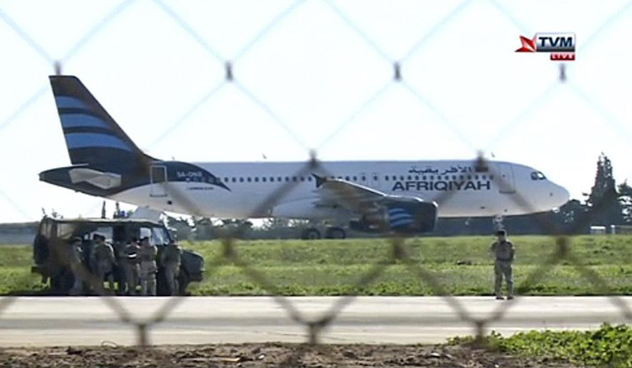 In this frame grab taken from television a hijacked Afriqiyah Airways A320 sits on the tarmac at Malta International airport Friday Dec. 23, 2016. Malta's state television says two hijackers who diverted a Libyan commercial plane to the Mediterranean island nation have threatened to blow it up. (Photo TVM via AP)