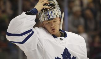 Toronto Maple Leafs goalie Frederik Andersen, of Denmark, pulls on his mask after a timeout against the Colorado Avalanche in the first period of an NHL hockey game Thursday, Dec. 22, 2016, in Denver. (AP Photo/David Zalubowski)