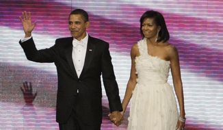 This Jan. 20, 2009, file photo shows President Barack Obama, left, and first lady Michelle Obama, in a one-shouldered white gown by designer Jason Wu, at the Neighborhood Inaugural Ball in Washington. (AP Photo/Alex Brandon, File)