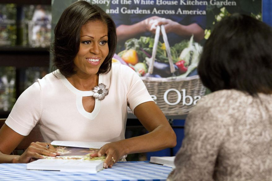"FILE - In this June 12, 2012, file photo, first lady Michelle Obama signs copies of her book ""American Grown: The Story of the White House Kitchen Garden and Garden Across America,"" in Washington. When Michelle Obama considered the daunting prospect of becoming first lady, she purposely avoided turning to books by her predecessors for guidance. Instead, she turned inward.  (AP Photo/Jacquelyn Martin, File)"