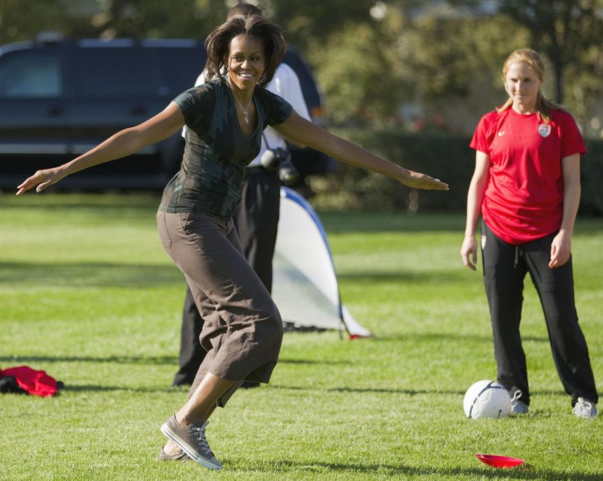 FILE - In this Oct. 6, 2011, file photo, first lady Michelle Obama plays soccer on the South Lawn of the White House in Washington, as part of a Let's Move! clinic. When Michelle Obama considered the daunting prospect of becoming first lady, she purposely avoided turning to books by her predecessors for guidance. Instead, she turned inward.  (AP Photo/Evan Vucci, File)